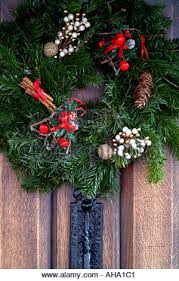 christmas wreath on oak front door of a traditional black white