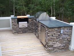 the outdoor kitchen soapstone countertop matches the kitchen
