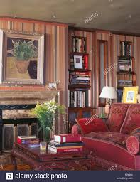 hardback books on coffee table beside fireplace and red sofa in