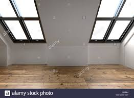 newly converted attic space interior with two sloping windows in newly converted attic space interior with two sloping windows in the pitch of the roof