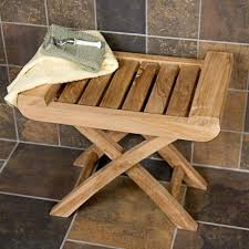 bathroom teak shower bench with x legs on travertine tile floor