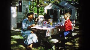 1959 multiracial family eating breakfast cereal outdoors camping