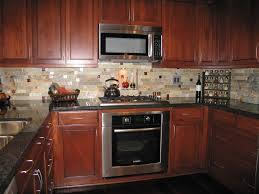 decorating brown kitchen cabinets with microwave and mosaic tile