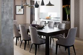 tom dixon pendant lighting over large table and gray upholstered