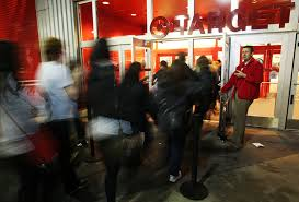 is target opening at midnight on black friday target employee holds the front door open while managing the rush