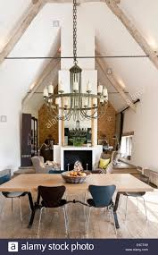 verdigris chandelier hangs above an oak topped dining table in