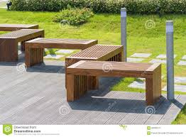 wood bench in garden with small green tree in background stock