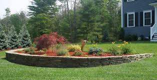 retainer wall and decorative plantings in front lawn to enhance