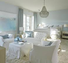 white and blue bedroom sitting area with gray beaded chandelier