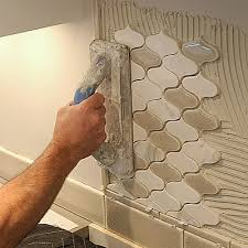 how to install a mosaic tile backsplash in the kitchen installing mosaic tile then firmly press it in place with a
