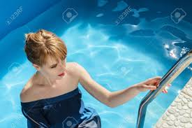 Inside Swimming Pool by Young Woman At Outdoor Fashion Photoshoot Demonstrating Luxurious