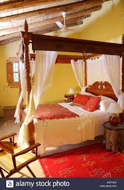 rustic wooden four poster bed in bedroom in spanish country villa