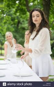 setting a table three women setting a table outside stock photo royalty free
