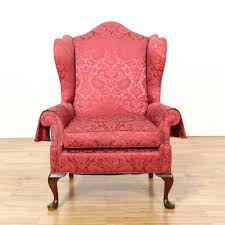 this wingback armchair is upholstered in a silk like fabric with a