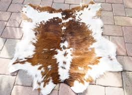 living room faux cowhide rug with brown wooden floor and small