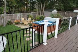 backyard with metal deck railing and tub outdoor deck