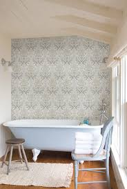 blue damask wallpaper feature wall in a bathroom with a clawfoot