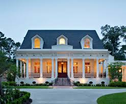 front door at dusk with cozy porch and white columns on new