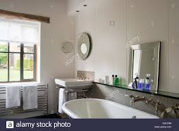 roll top bath in white bathroom with glass shelf and mirrors stock