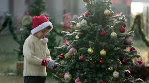 beautiful child boy decorating christmas tree on a frosty