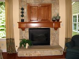 beige stone fireplace with brown wooden mantel shelf and rectangle