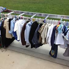 great idea for displaying clothes at a garage sale turn a ladder