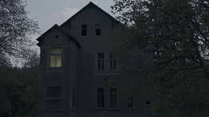 spooky house in a woods with eeerie windows shot at night stock