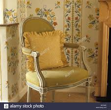 close up of french style yellow upholstered dining chair with