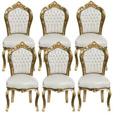 6 chairs made of white leatherette and gold wood dining room
