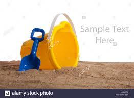 yellow beach bucket and blue shovel on a sandy beach with copy