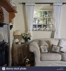 white curtains on window above white sofa in nineties cottage