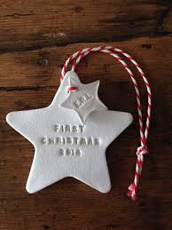 a white clay hanging decoration hand printed with first christmas