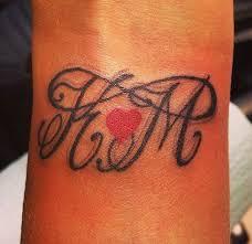 infinity tattoo w large initials u0026 small red heart on wrist