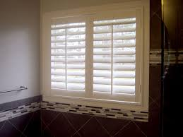 decorating travertine tile with plantation blinds and towel bar