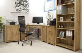 gorgeous corner solid oak desks for home office which is installed below black painting of branches and tall bookshelves also black colored office chairs jpg