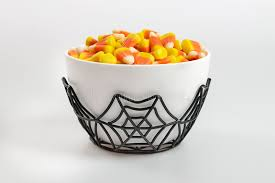 a bowl full of halloween candy corn on a white background stock