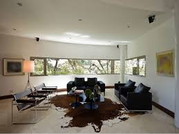 living room brown cowhide rug with black sofa for decorating ideas