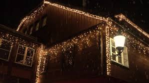 christmas lights that look like snow falling slow motion close up big wooden family house decorated with white