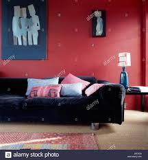 blue art and blue velvet sofa against plum red wall in sitting