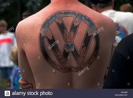 man with vw tattoo on back squats among car parts on tarp at