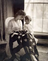 American Flag Watches File A Child Watches As A Woman Sews A Star On A United States