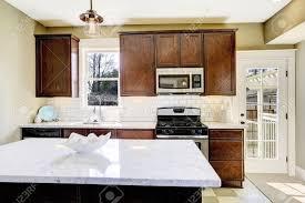 kitchen room with steel appliances white tile back splash trim