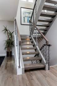 metal landing banister and railing custom floating stair case with hardwood treads and a metal rail