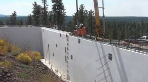 pouring concrete in a 12 inch retaining wall built using fox