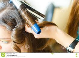 closeup of hairdresser doing the styling for a festive evening of