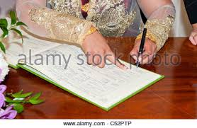 register wedding and groom signing wedding register during a civil wedding