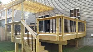 outdoor wooden deck with attached pergola and aluminum balusters