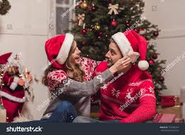 happy young couple santa hats smiling stock photo 715100374