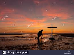 a praying by a black cross with a flowing water around it