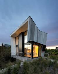 a two story beach house with a small footprint design milk